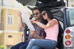 Homme et femme de touristes heureux dans la voiture Images stock