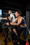 Homme et femme elliptiques d'entraîneur de marcheur au gymnase noir Image stock