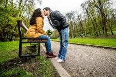 Homme et femme embrassant et embrassant sur le banc en parc vert de ressort Image libre de droits