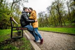 Homme et femme embrassant et embrassant sur le banc en parc vert de ressort Photos libres de droits
