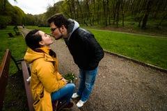 Homme et femme embrassant et embrassant sur le banc en parc vert de ressort Photographie stock libre de droits