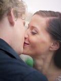 Homme et femme embrassant et souriant Image stock