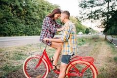 Homme et femme embrassant sur le rétro vélo Photo stock