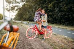 Homme et femme embrassant sur le rétro vélo Photographie stock libre de droits