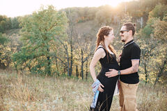Homme et femme enceinte étreignant tenant des mains sur le fond de la nature sauvage, automne Histoire d'amour Images stock