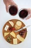 Homme et femme encourageant avec du vin au-dessus d'un plateau de fromage Photos stock
