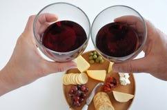 Homme et femme encourageant avec du vin au-dessus d'un plateau de fromage Image stock