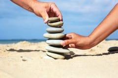 Homme et femme ensemble pour construire une tour faite de pierres Photo stock