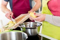Homme et femme faisant cuire le plat végétarien ensemble Photographie stock libre de droits