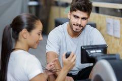 Homme et femme faisant des exercices avec la machine à ramer au gymnase photo stock