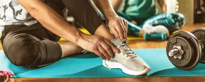 Homme et femme faisant la séance d'entraînement dans la contre-clavette sur des tapis de yoga photographie stock