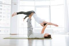 Homme et femme faisant le yoga d'acro dans les paires dans le studio Photographie stock