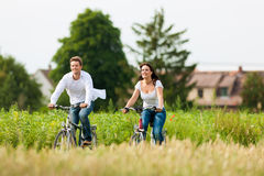 Homme et femme faisant un cycle en été Image libre de droits