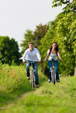 Homme et femme faisant un cycle en été Photos stock