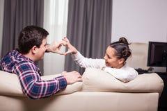Homme et femme faisant un symbole de coeur à partir de leurs doigts Photo libre de droits