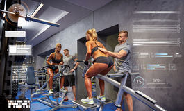Homme et femme fléchissant des muscles sur la machine de gymnase photographie stock
