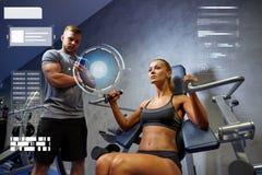 Homme et femme fléchissant des muscles sur la machine de gymnase images stock