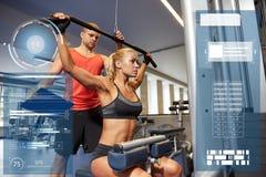 Homme et femme fléchissant des muscles sur la machine de gymnase image stock
