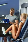 Homme et femme fléchissant des muscles sur la machine de gymnase Photographie stock libre de droits