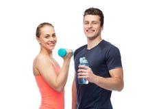 Homme et femme folâtres avec de l'eau l'haltère et Photographie stock libre de droits