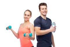 Homme et femme folâtres avec de l'eau l'haltère et Photographie stock