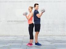 Homme et femme folâtres avec des haltères Photos stock