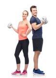 Homme et femme folâtres avec des haltères Photographie stock libre de droits