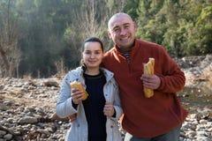 Homme et femme gaie mangeant des sandwitches au pique-nique dehors Photos libres de droits