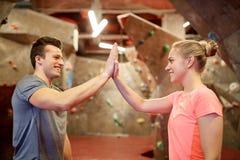 Homme et femme heureux au mur s'élevant d'intérieur de gymnase Photo stock