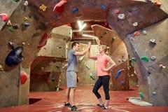 Homme et femme heureux au mur s'élevant d'intérieur de gymnase Photographie stock