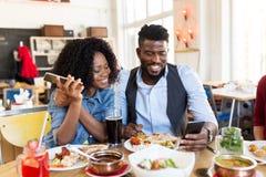 Homme et femme heureux avec des smartphones au restaurant Photo stock