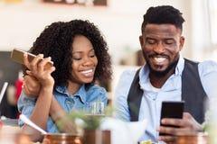 Homme et femme heureux avec des smartphones au restaurant Images libres de droits