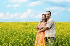 Homme et femme heureux dans le pré jaune photo stock