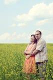 Homme et femme heureux dans le pré jaune photographie stock libre de droits