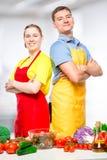homme et femme heureux dans les tabliers préparant la salade végétale images stock