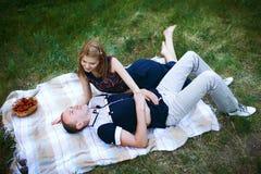 Homme et femme heureux sur le plaid Photographie stock