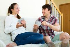 Homme et femme jouant des cartes Images stock