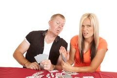 Homme et femme jouant des cartes qu'il jette un coup d'oeil Photo libre de droits