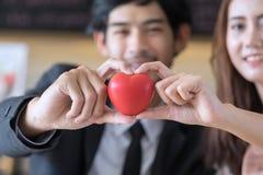 Homme et femme jugeant le coeur rouge disponible images stock