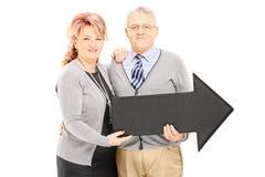 Homme et femme mûrs de sourire tenant une grande flèche se dirigeant juste Images libres de droits