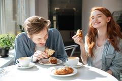 Homme et femme mangeant des desserts en café Photographie stock libre de droits