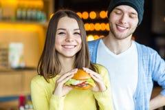 Homme et femme mangeant l'hamburger La jeune fille et le jeune homme tiennent des hamburgers sur des mains Photo stock