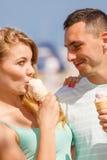 Homme et femme mangeant la crème glacée sur la plage Photographie stock