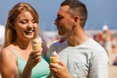 Homme et femme mangeant la crème glacée sur la plage Image libre de droits