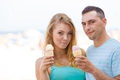 Homme et femme mangeant la crème glacée sur la plage Photos stock