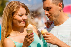 Homme et femme mangeant la crème glacée sur la plage Photo libre de droits