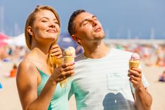 Homme et femme mangeant la crème glacée sur la plage Images libres de droits