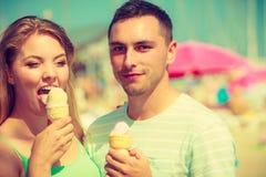 Homme et femme mangeant la crème glacée sur la plage Photo stock