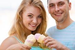 Homme et femme mangeant la crème glacée sur la plage Photographie stock libre de droits