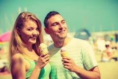 Homme et femme mangeant la crème glacée sur la plage Images stock